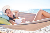 Brunette relaxing in the hammock and smiling at camera