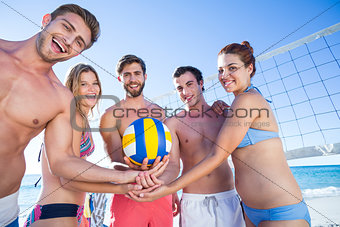 Group of friends holding volleyball and smiling at camera