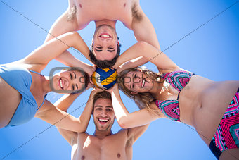 Group of friends standing in circle and holding ball