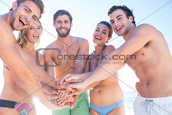 Group of friends standing in circle and smiling at camera