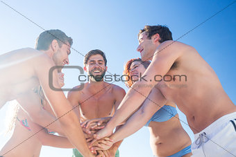 Group of friends standing in circle hands together