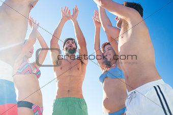 Group of friends standing in circle arms raised