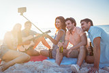 Happy hipsters taking pictures with selfie stick