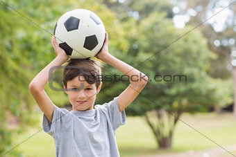 Smiling boy holding a soccer ball in the park