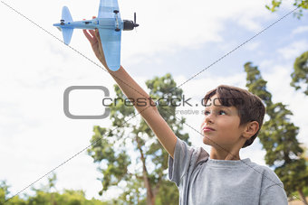 Boy playing with a toy plane at park