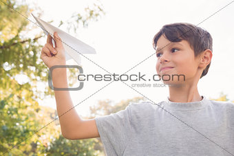 Smiling boy with paper plane in the park