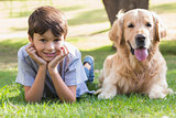 Little boy looking at camera with his dog in the park