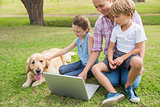 Happy family with their dog using laptop