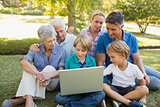 Happy family using laptop in the park