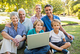 Happy family smiling at camera and using laptop in the park