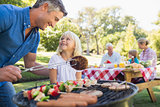Happy father doing barbecue with her daughter