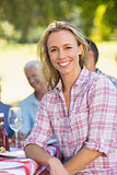 Pretty blonde woman smiling at camera during a picnic