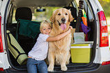 Smiling little girl with her dog in car trunk