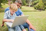 Happy father with his son using laptop in the park