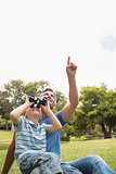 Father and his son using binocular in the park