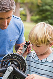 Father and his son fixing a bike