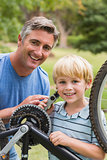Happy father and his son fixing a bike