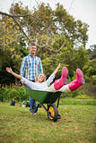 Happy couple playing with a wheelbarrow