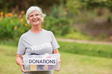 Happy grandmother holding donation box