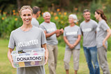 Happy volunteer holding donation box