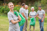Happy volunteer collecting rubbish