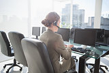 Smiling businesswoman with headset using computers