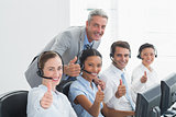 Colleagues with headsets using computers while gesturing thumbs up