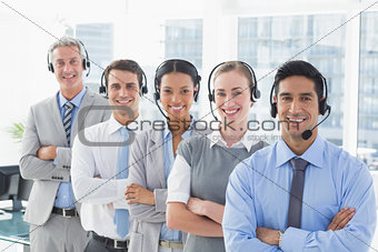 Business people with headsets smiling at camera