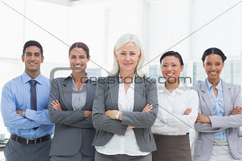 Business people with arms crossed smiling at camera
