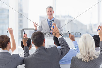 Business people raising their arms during meeting