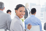 Businesswoman looking at camera during meeting