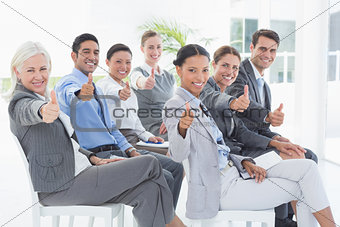 Business people looking at camera with thumbs up