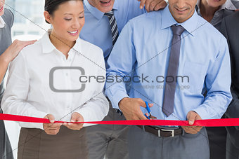 Business man cutting red strip