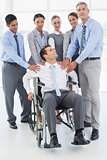 Businessman in wheelchair with his colleagues looking at camera