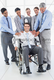 Business people supporting their colleague in wheelchair