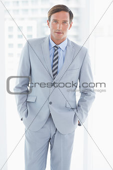 portrait of businessman looking at camera with hands in pockets