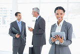 Businesswoman using a tablet with colleagues behind in office