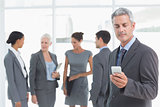 Businessman using mobile phone with colleagues behind