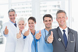 Portrait of confident doctors in row thumbs up