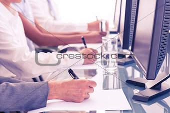 Close up view of business people writing on paper
