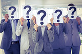 Business team holding question marks over face
