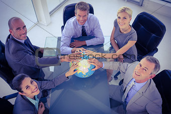 Business team putting hands on globe
