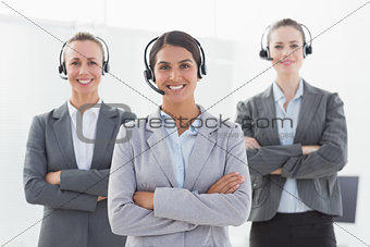 Business team wearing headsets and standing arms crossed
