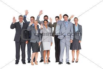 Smiling business team waving at camera