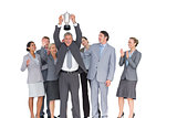 Excited business team cheering at camera with trophy