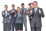 Smiling business team showing thumbs up