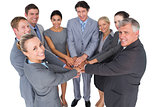 Smiling business team standing in circle hands together