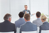 Pretty businesswoman talking in microphone during conference