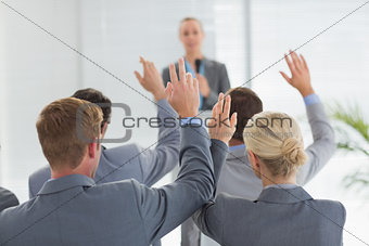 Business team raising hands during conference