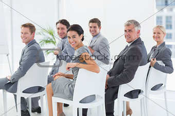 Smiling business team looking at camera during conference